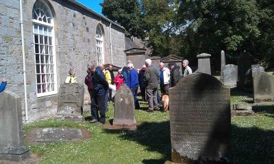 Members of Currie History Society examine a headstone in Currie Kirkyard (June 2011)